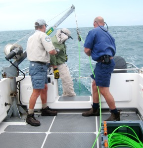 The magnetometer being deployed from the Queensland Marine Parks vessel Caretta.  Assisting are Ranger Rohan Couch (left) and Technical Officer James Fels (right).